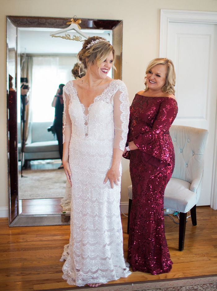 mom helping bride get dressed